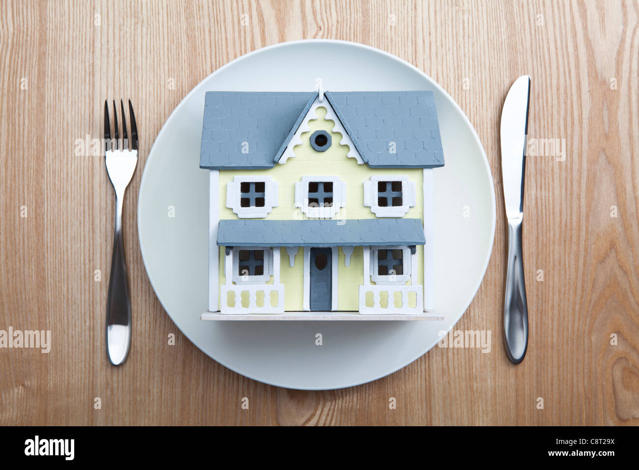 Top view of architectural model placed in plate with fork and knife on table Stock Photo