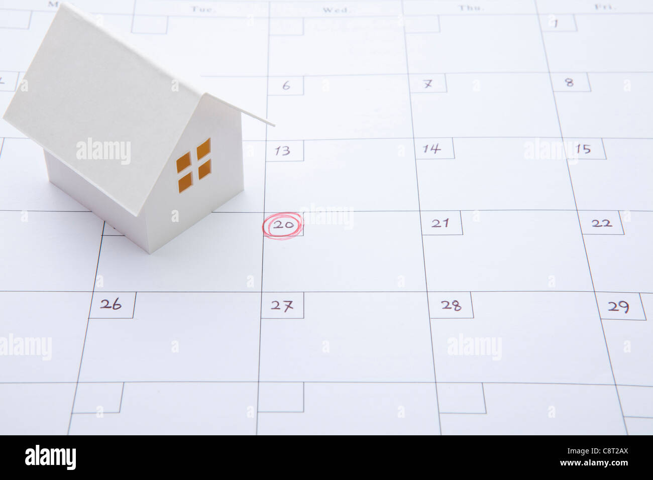 Model of house on calendar with marking on 20th of the month - Stock Image