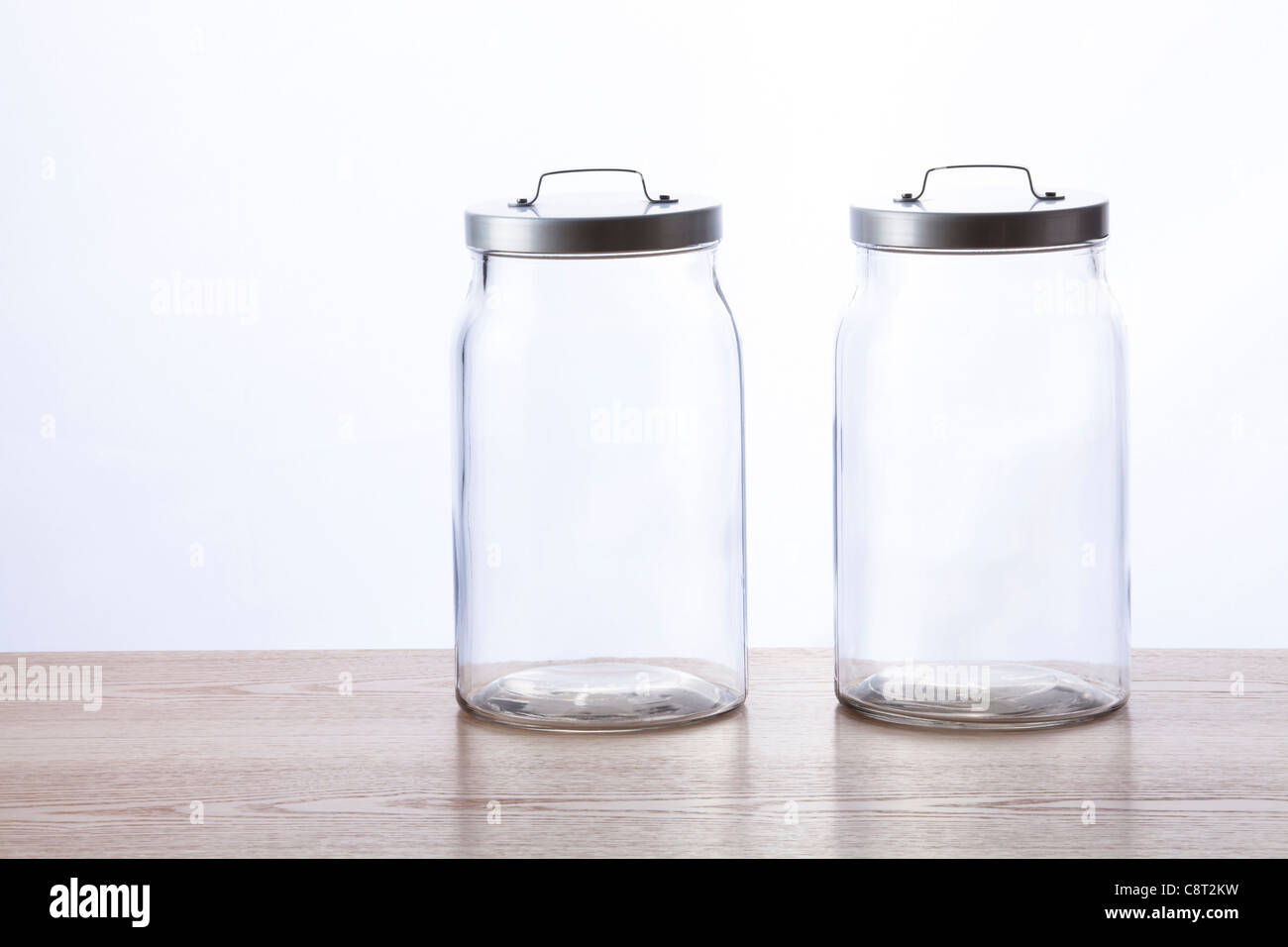 Two empty glass jar with lid closed against white background - Stock Image