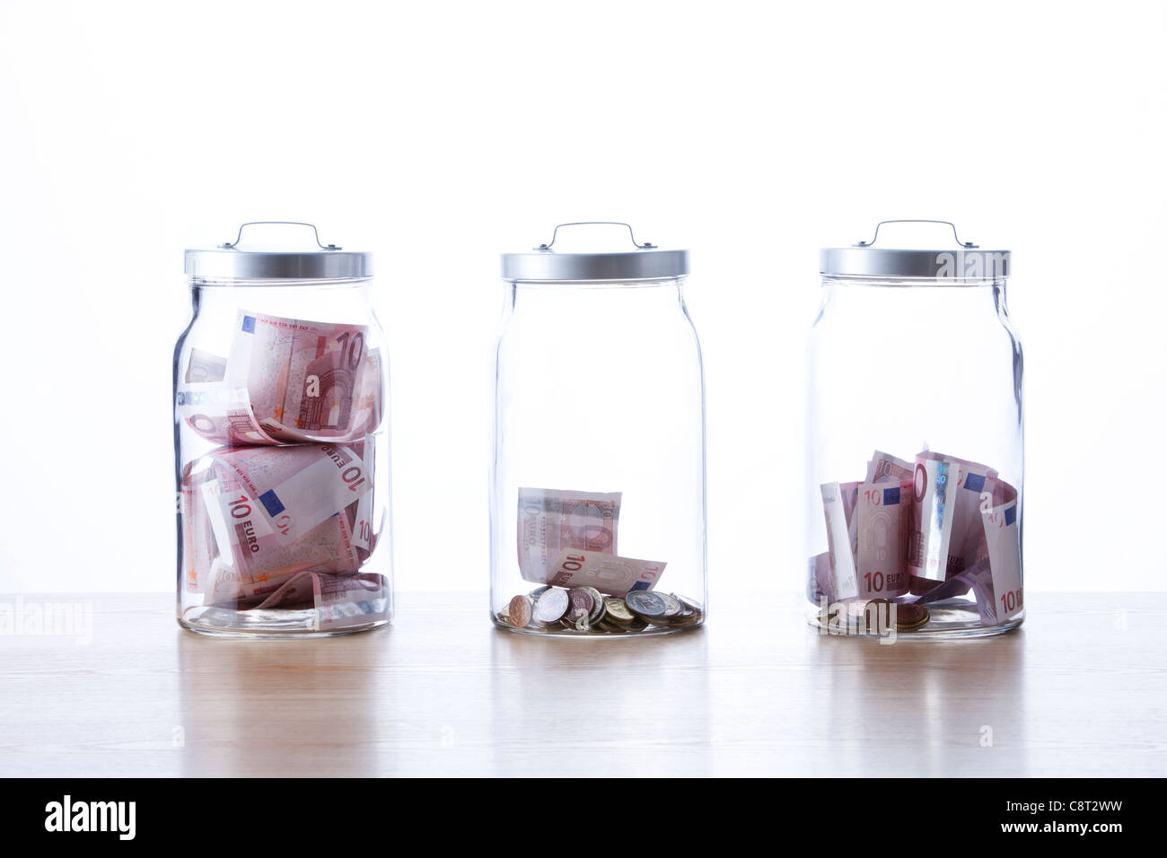 Three glass jars filled with European union currency against white background - Stock Image
