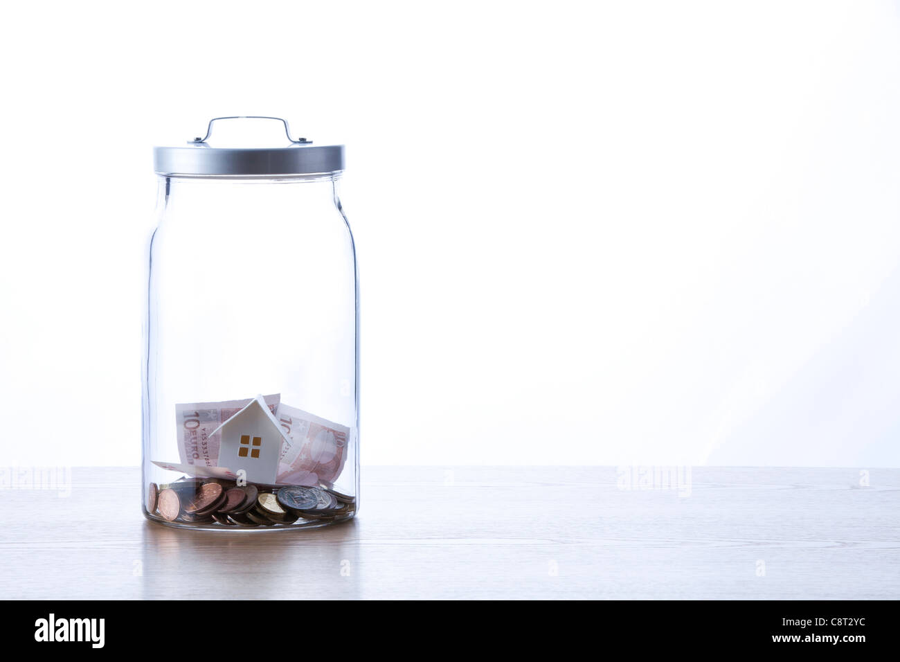 European union currency and model house inside of glass jar - Stock Image