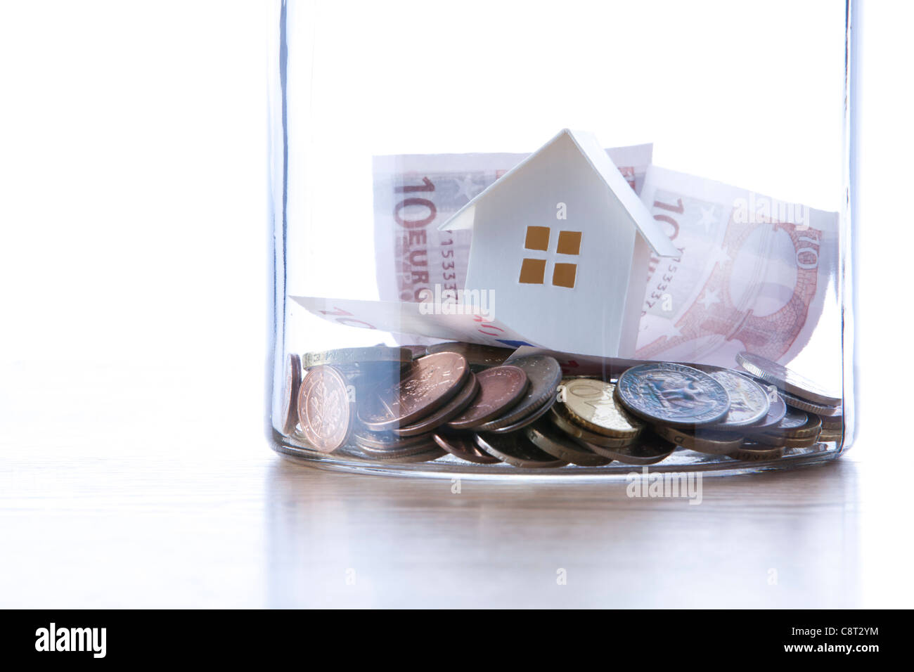 Close up of European union currency and model home in glass jar - Stock Image