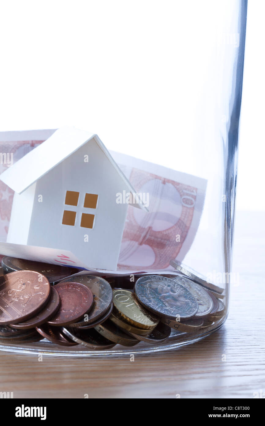 Close up of European union currency and model home in glass jar against white background - Stock Image