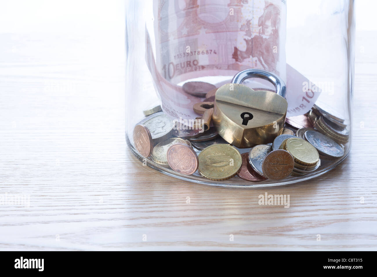 Close-up of European union currency with lock and key in glass jar - Stock Image