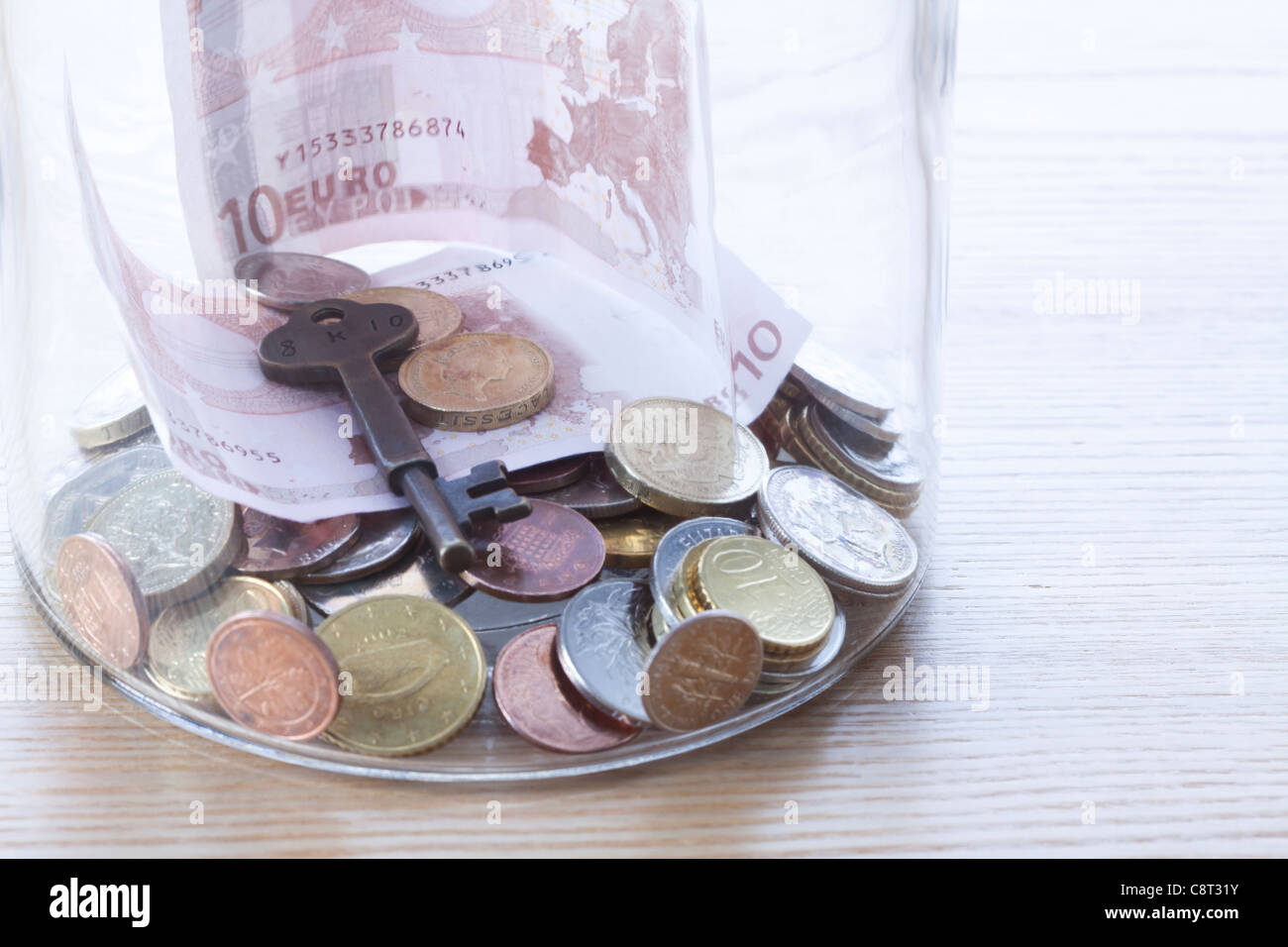 Close-up of European union currency and key in glass jar - Stock Image