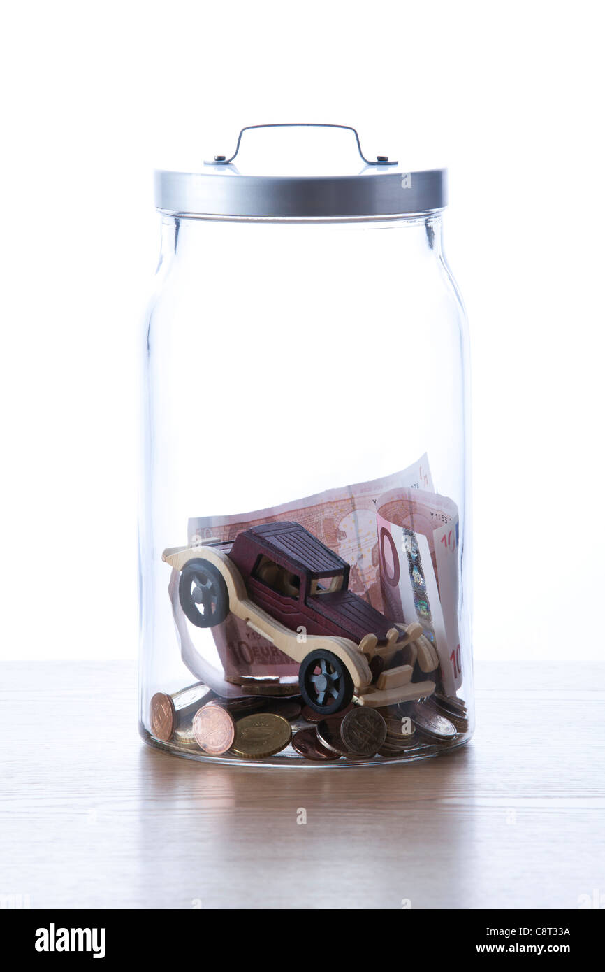 Dummy car inside of glass jar with European union currency - Stock Image