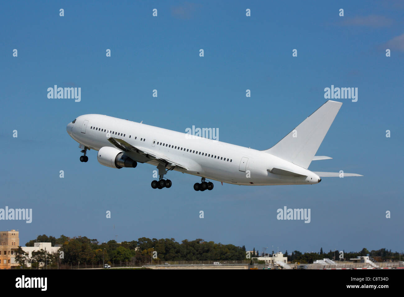 Boeing 767 large commercial passenger jet plane taking off against a clear blue sky. No livery and proprietary details - Stock Image