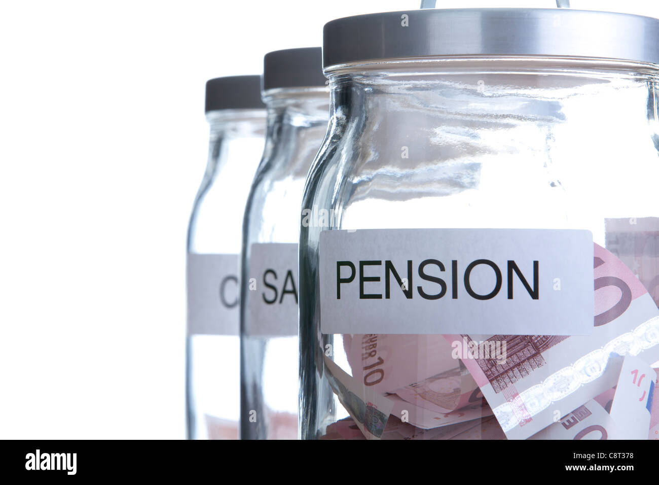 Close-up of three glass jar showing sources of money - Stock Image