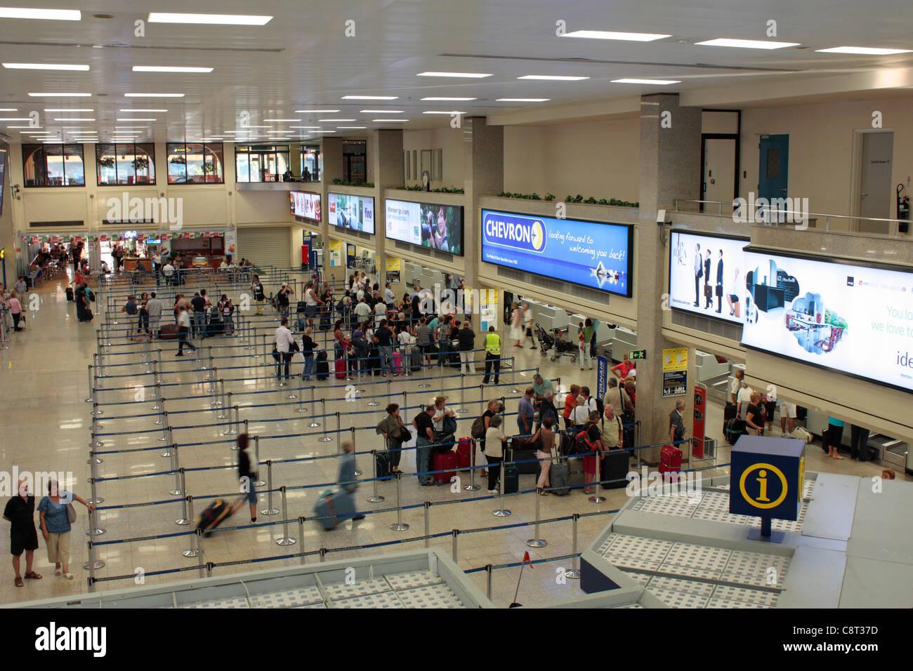 Passengers waiting to check in at Malta International Airport - Stock Image
