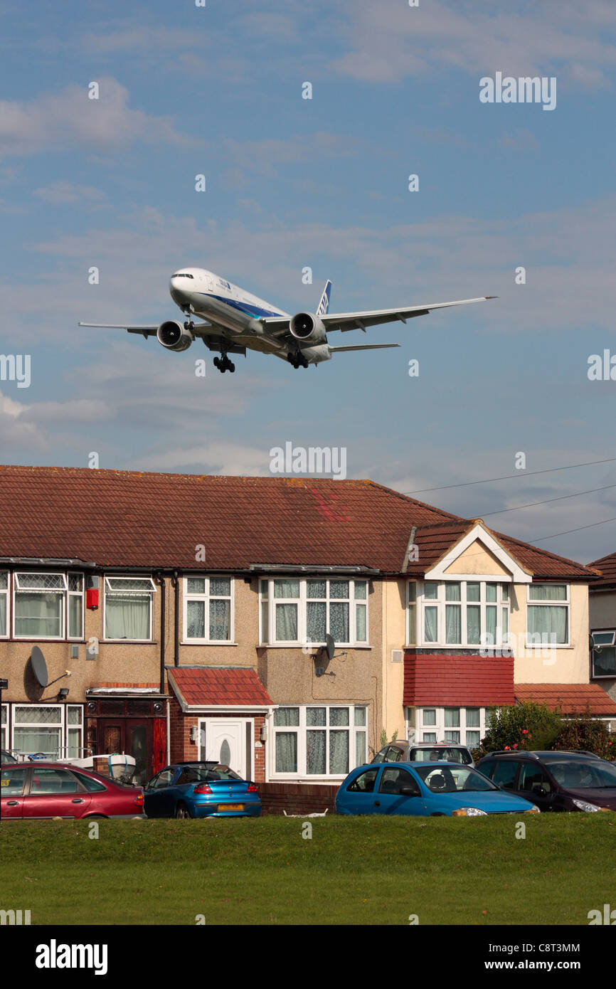 ANA Boeing 777-300ER overflying a residential area on final approach to Heathrow Airport - Stock Image