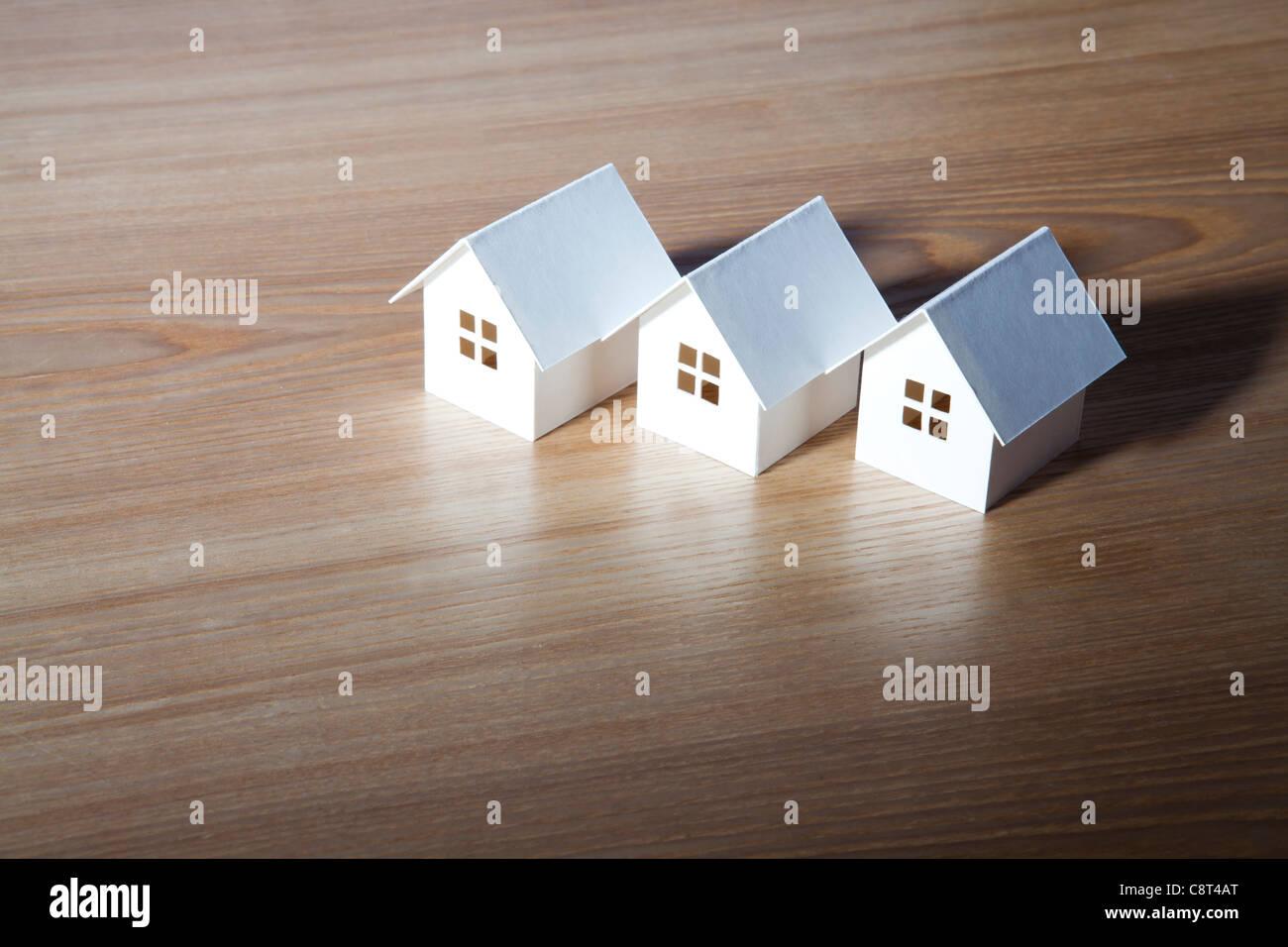Three white model home kept on table - Stock Image