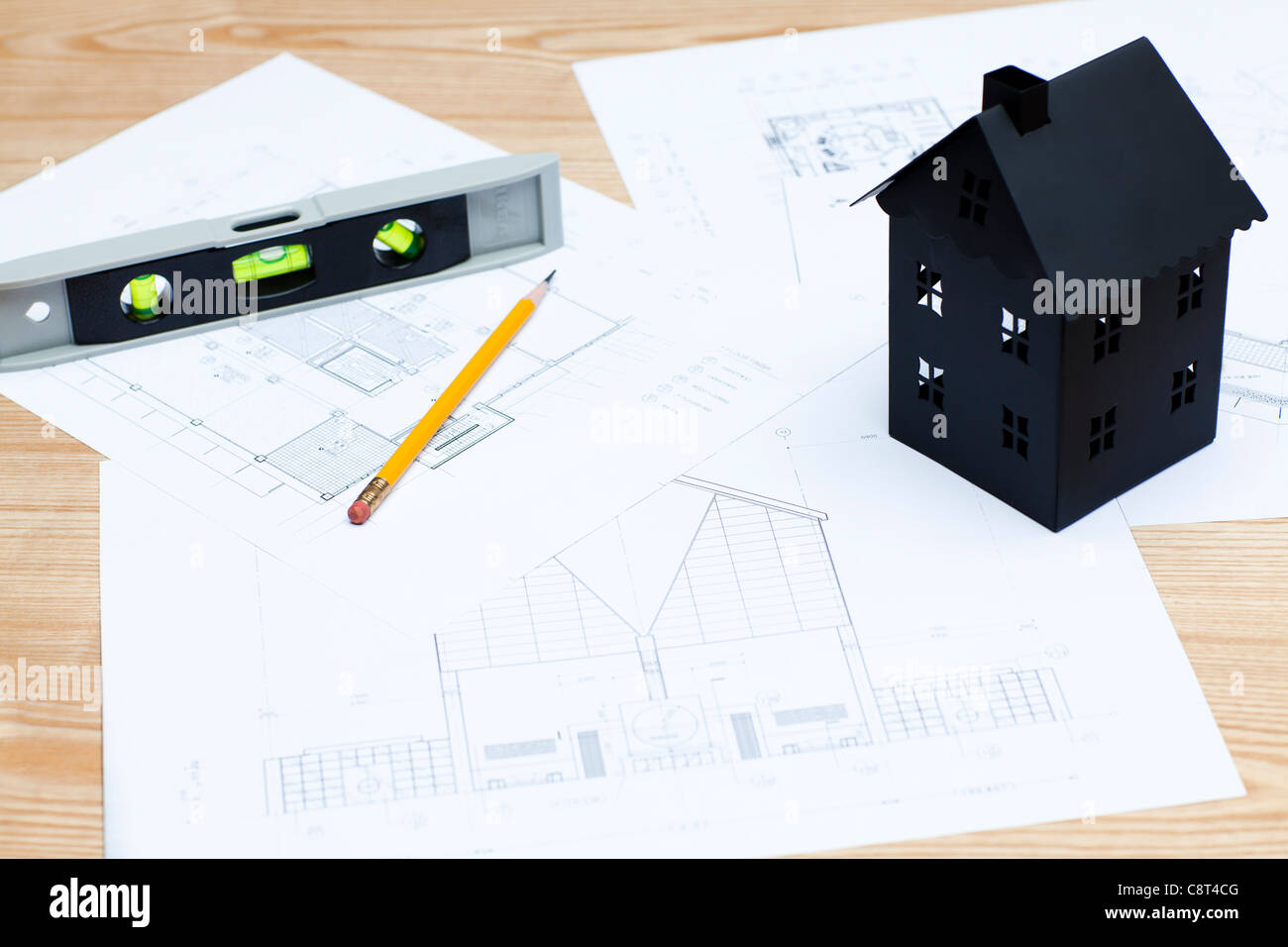 Model home on blueprint along with pencil and spirit level - Stock Image