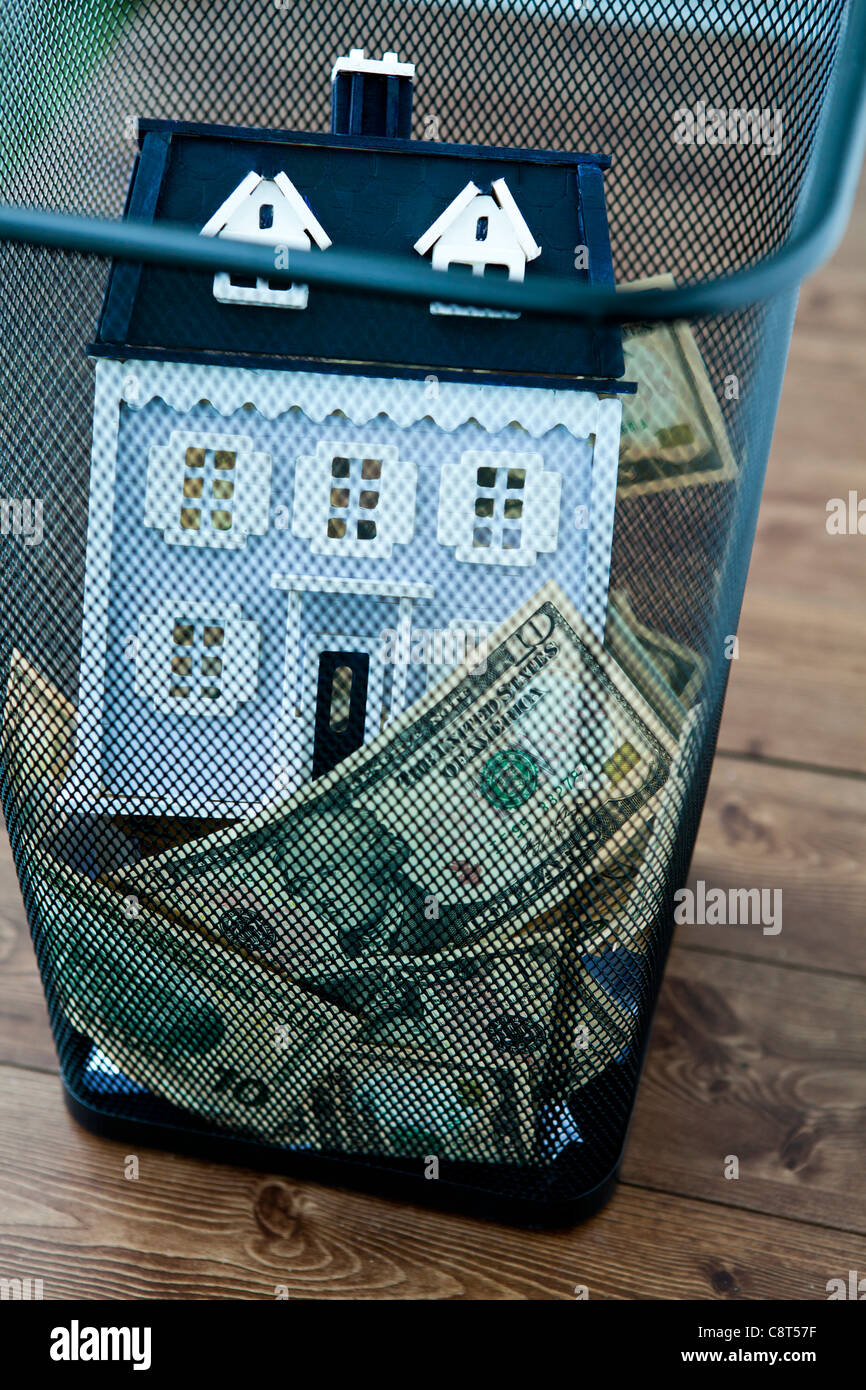 American dollar bills and model home in garbage can - Stock Image