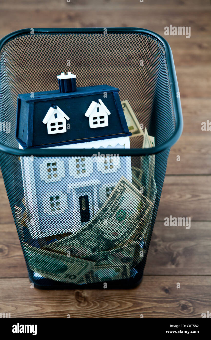 Money and model home in garbage can - Stock Image