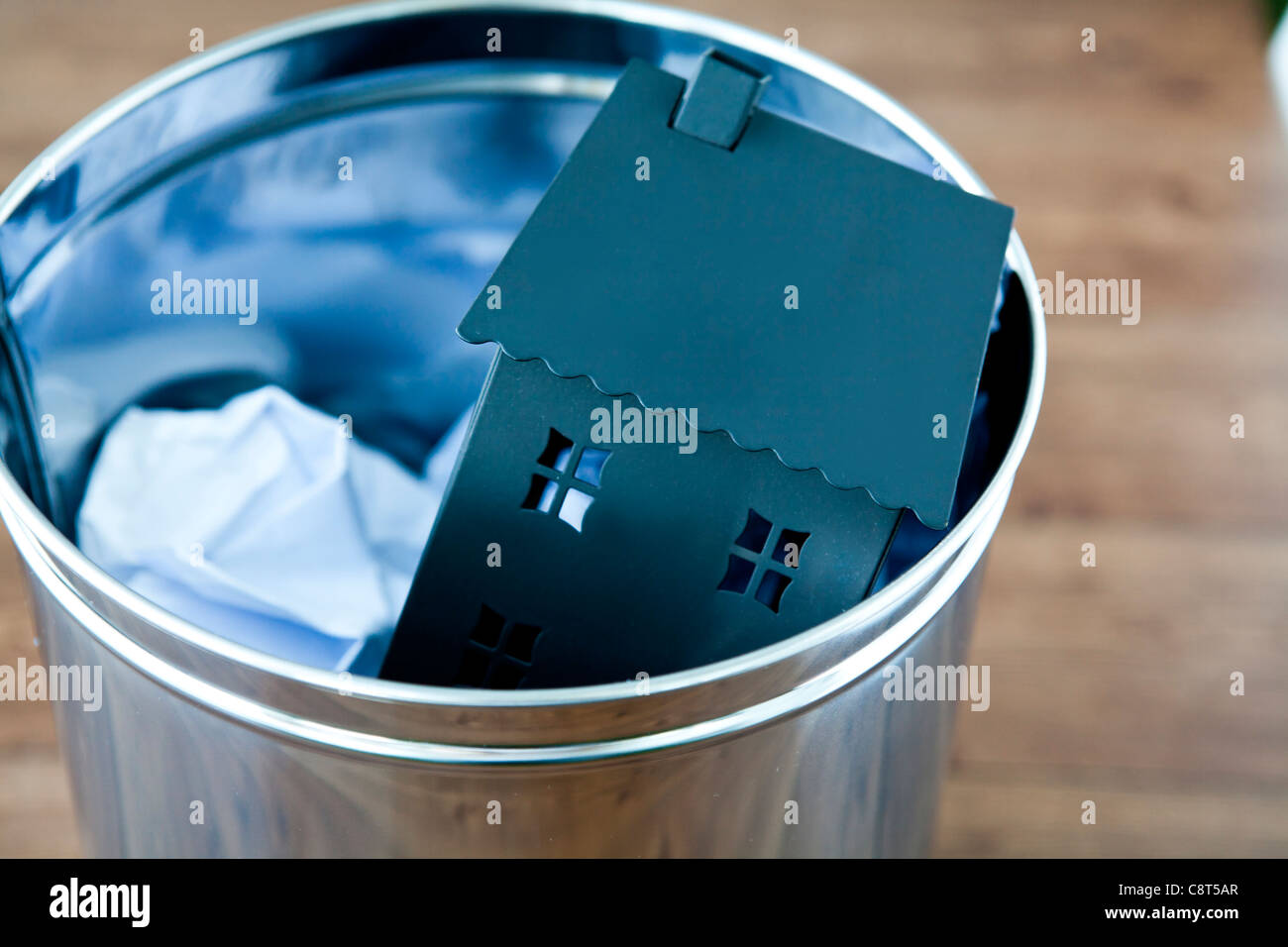 Model of house and crumbled paper in garbage can - Stock Image