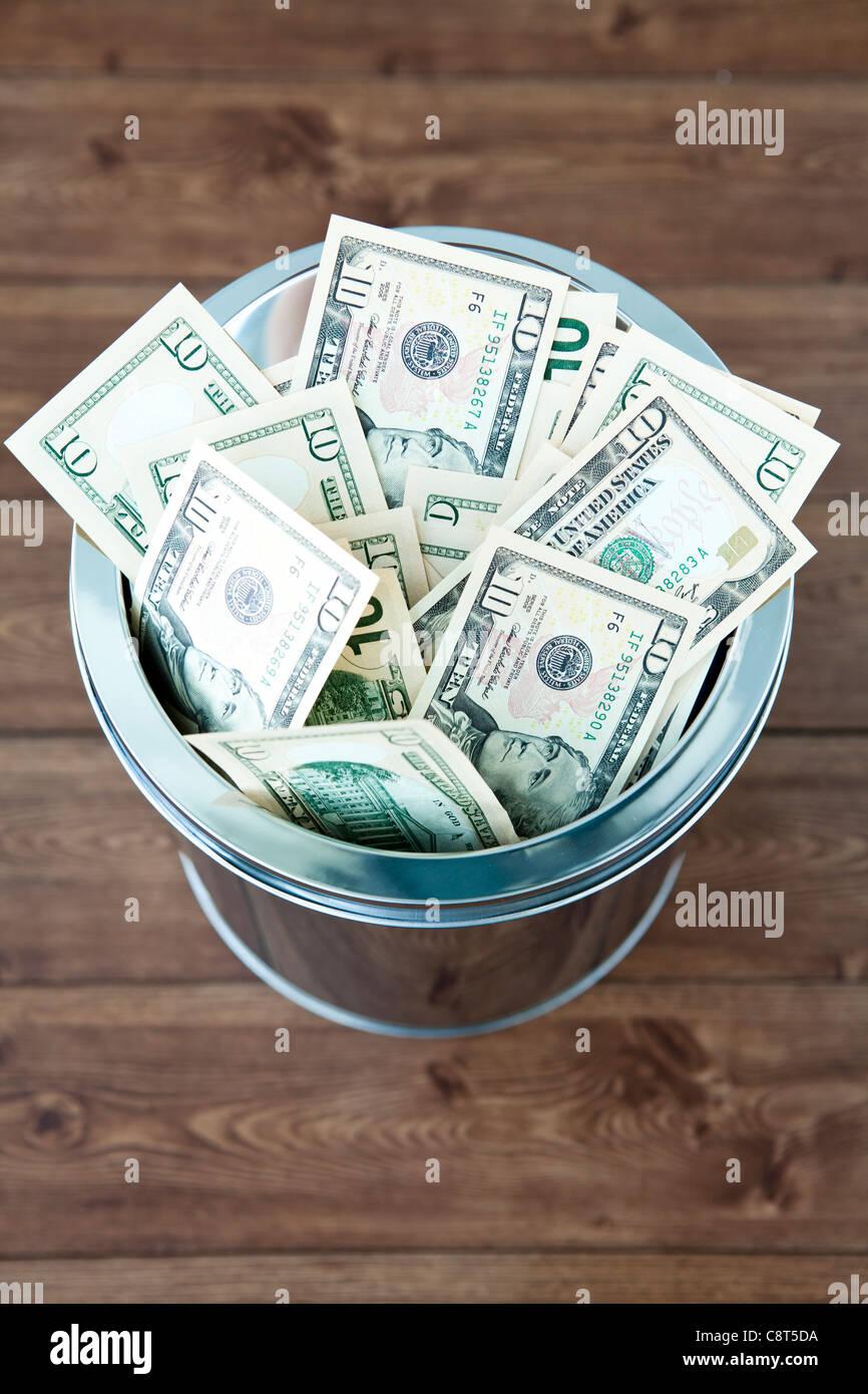 American ten dollar bills in garbage can - Stock Image