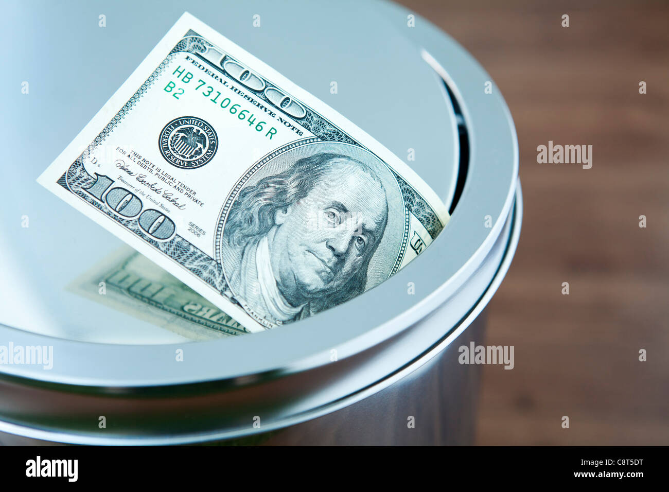Hundred dollar bill in garbage can - Stock Image