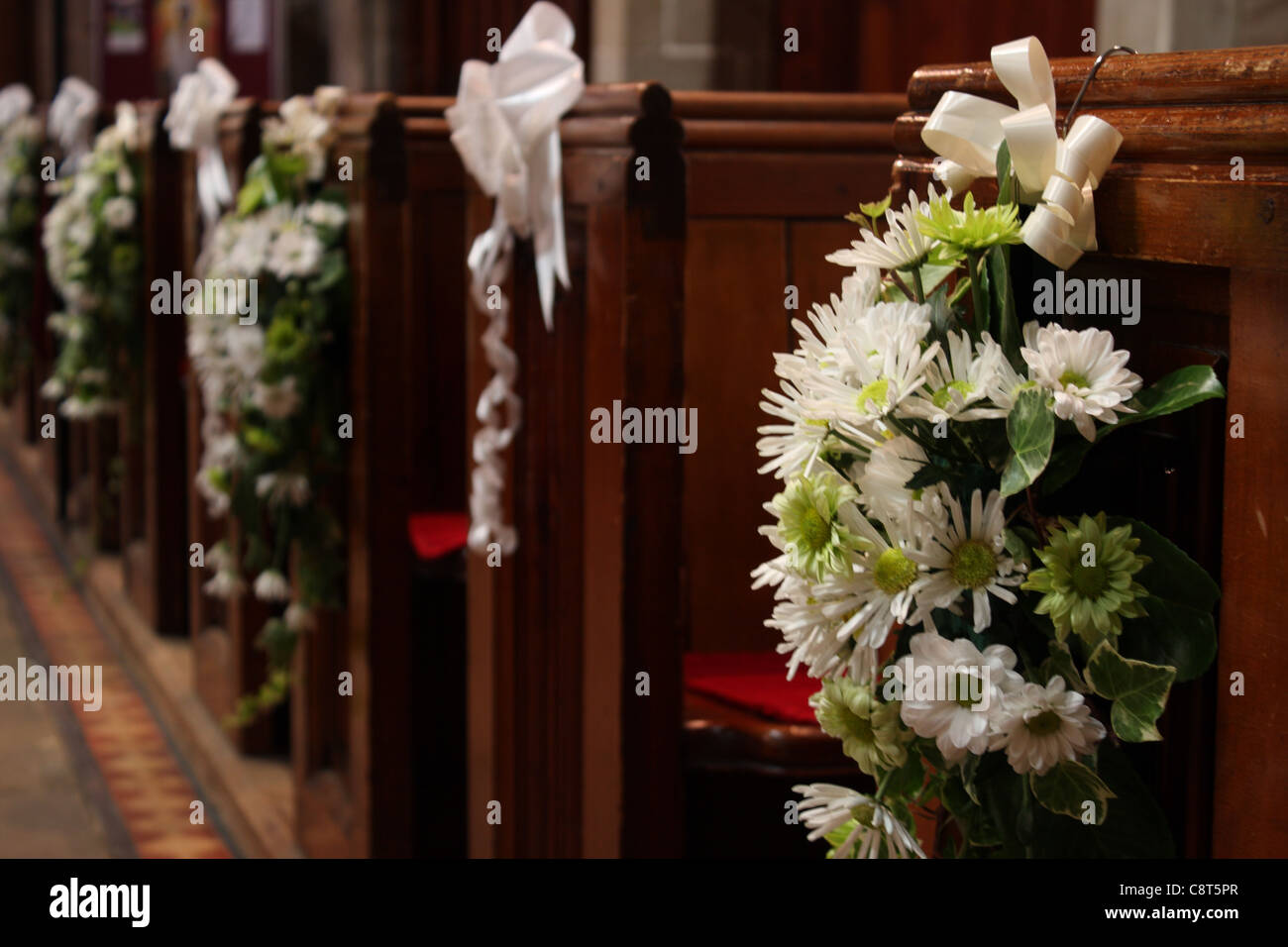 church pews with wedding floral arrangements of flowers in