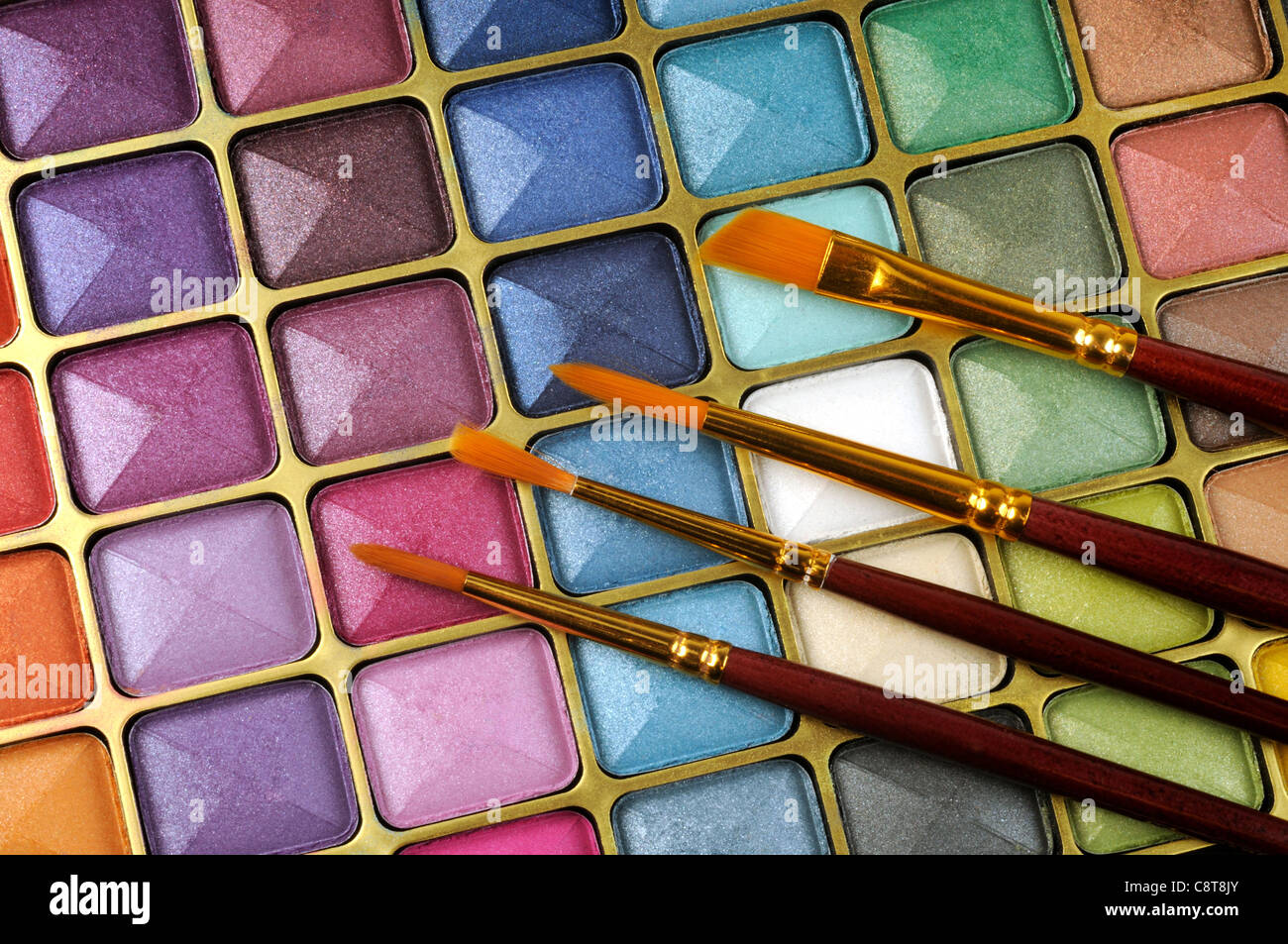Decorative colorful eyeshadow and brushes , close up shot - Stock Image