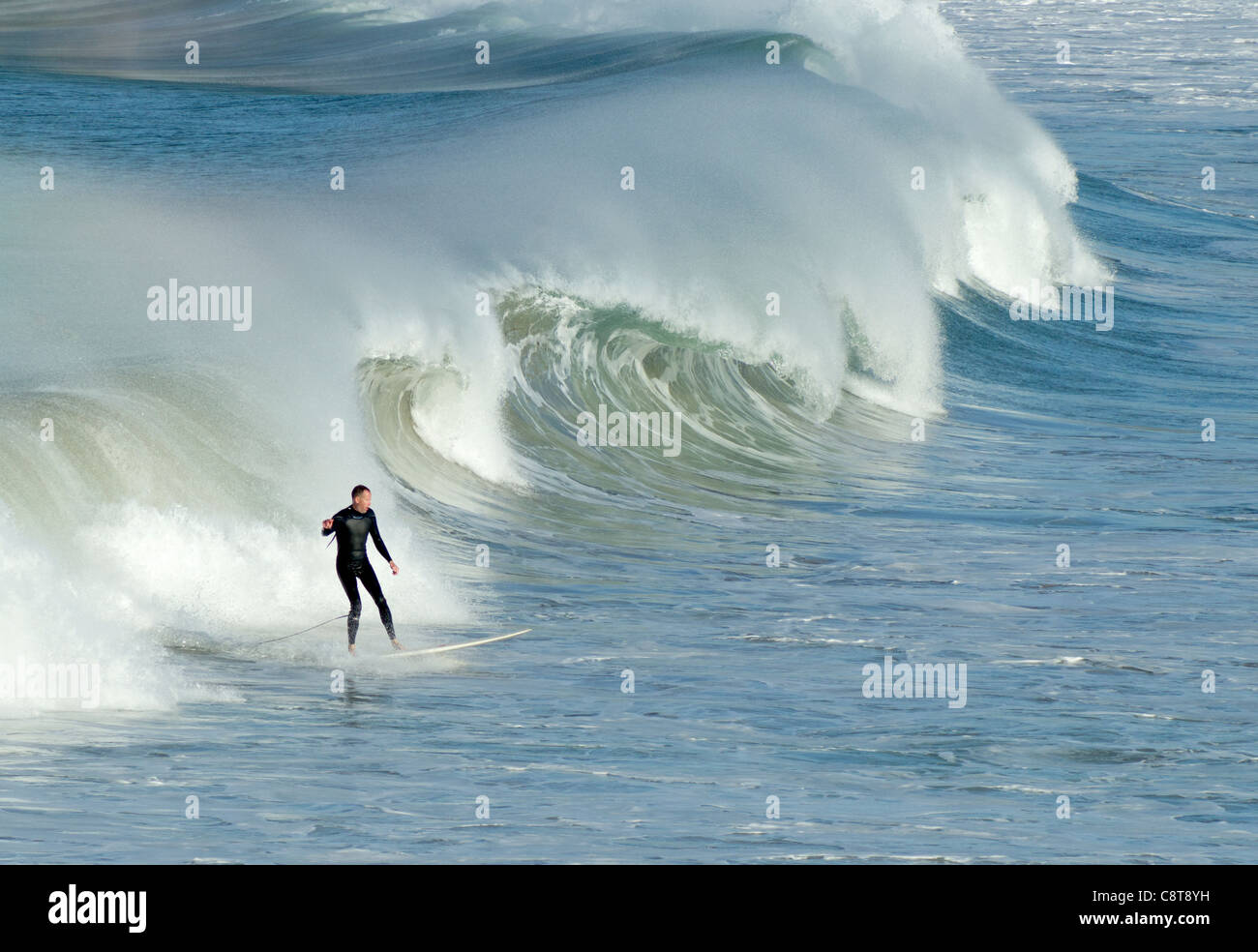 A surfer surfing a breaking wave with lots of water spray in Newquay, Cornwall UK. - Stock Image