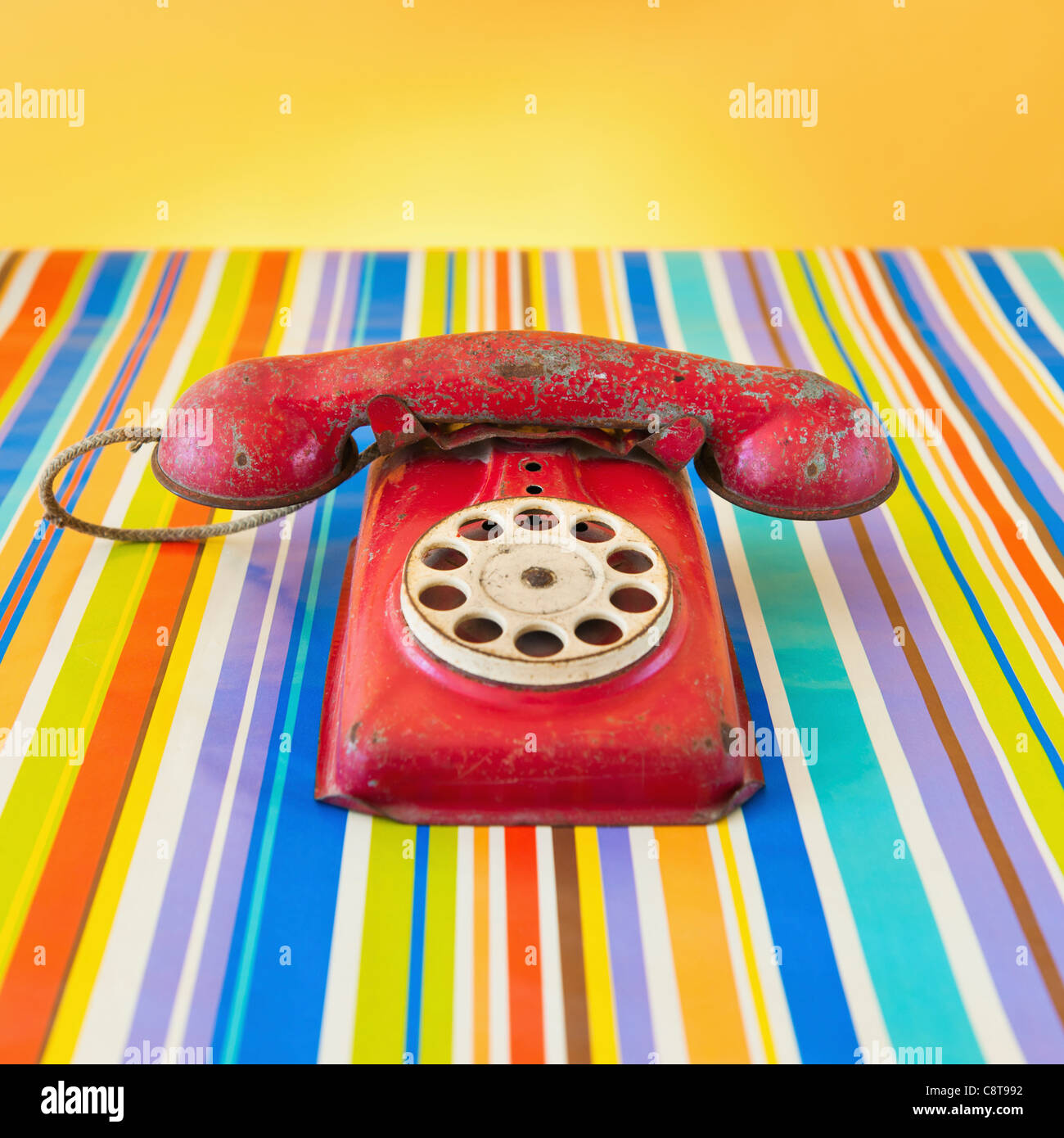 Studio shot of rotary phone on striped background - Stock Image