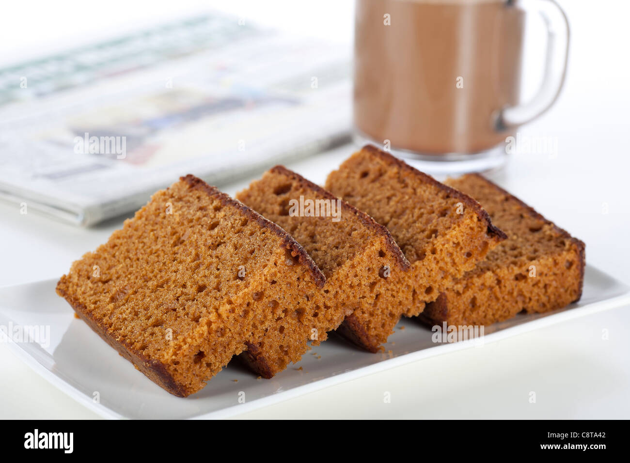Dutch breakfast cake, often spiced with cloves cinnamon and nutmeg. A coffee and newspaper in the background. - Stock Image