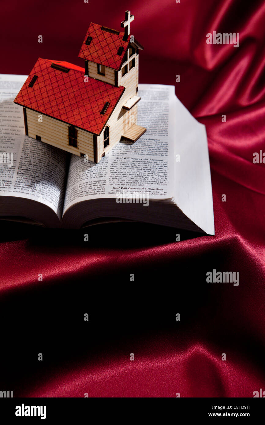 High angle view of model of church on bible with magenta cloth in the background - Stock Image