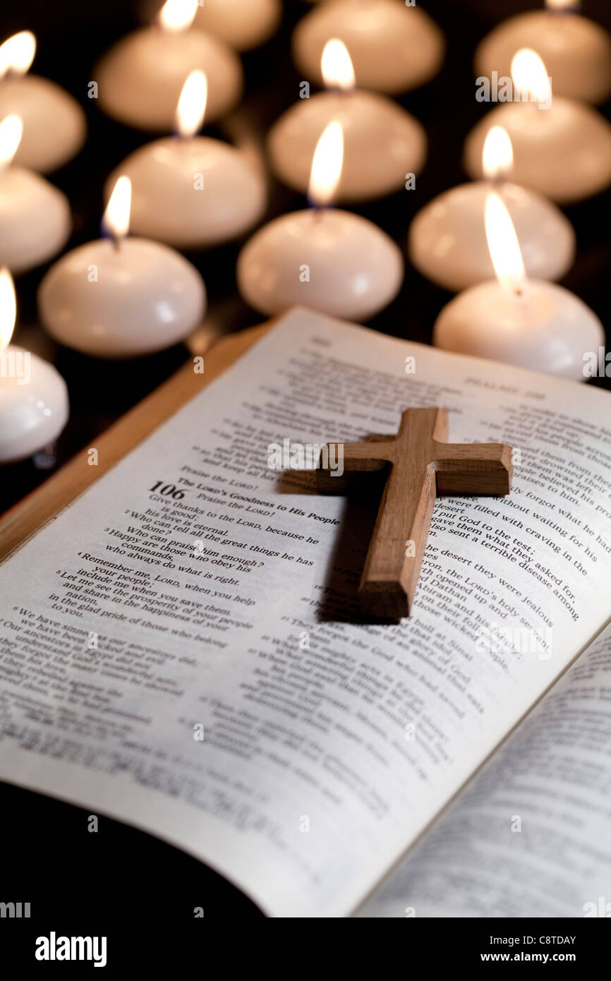 cross lying on holy bible with candles in the background stock photo