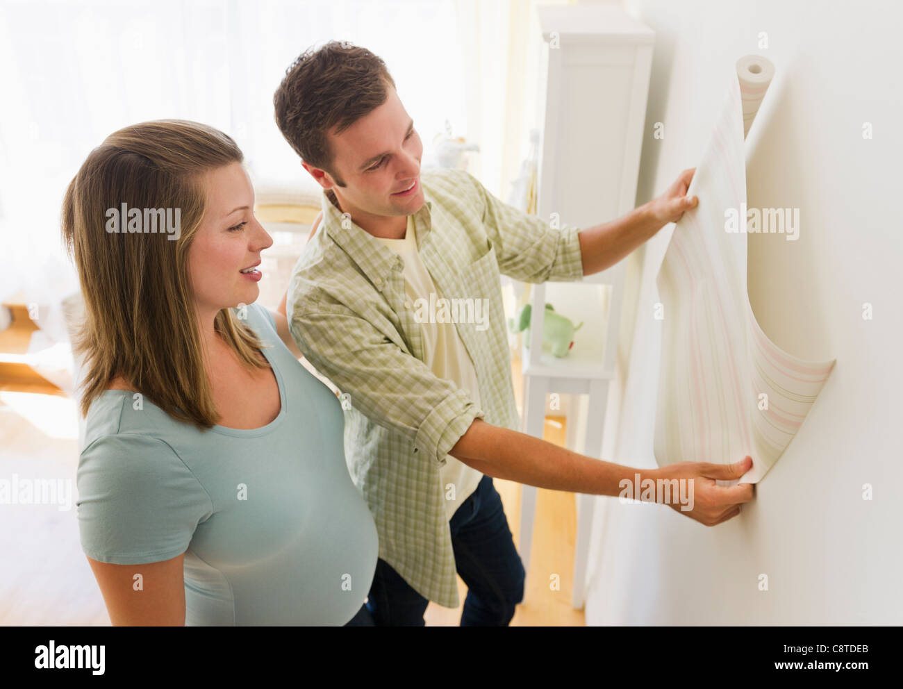 Young pregnant couple looking at wallpaper in nursery - Stock Image