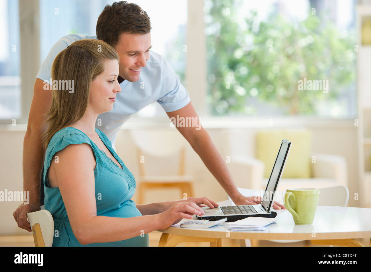 USA, New Jersey, Jersey City, Young couple using laptop - Stock Image