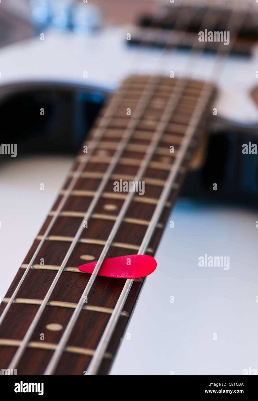 Close-up of bass guitar with guitar pick - Stock Image