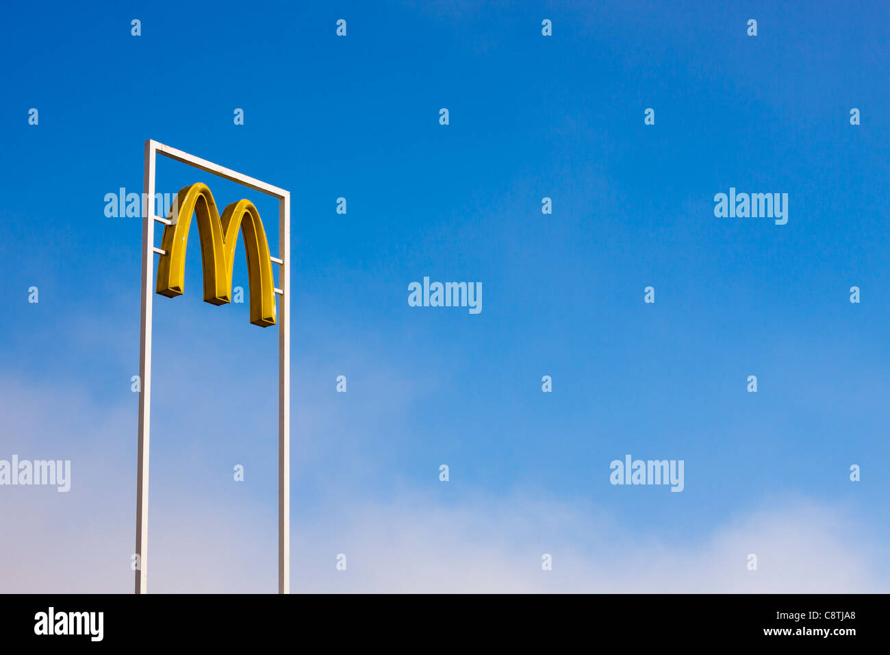 McDonalds sign over bright blue sky. - Stock Image