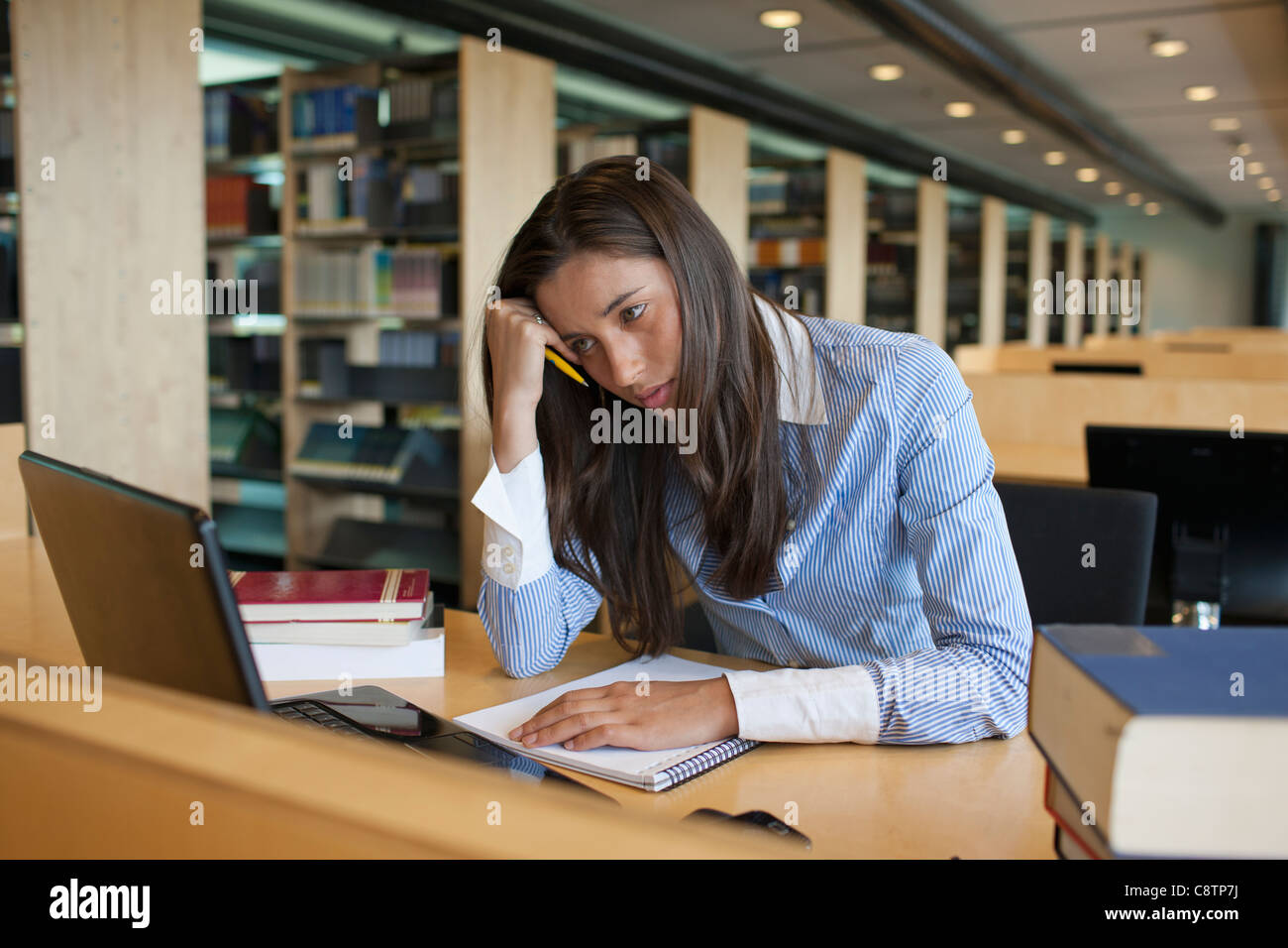 Netherlands, Maastricht, Female student studying in library Stock Photo