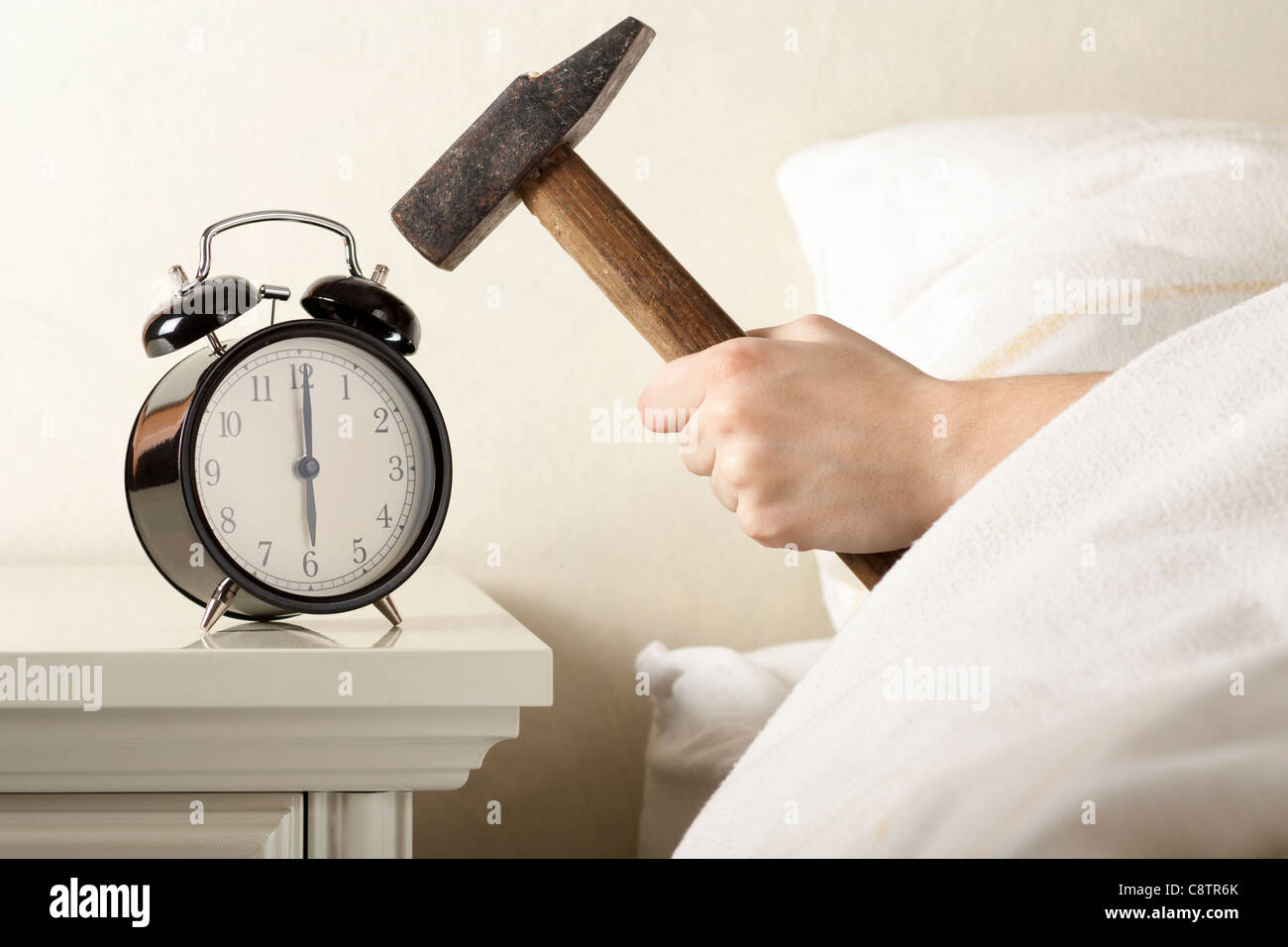 Crushing Alarm Clock with Hammer - Stock Image