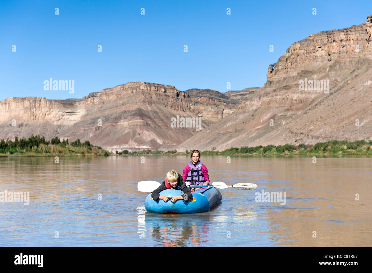 Mother and child enjoy paddling down the Oranje River at Noordoewer Namibia - Stock Image