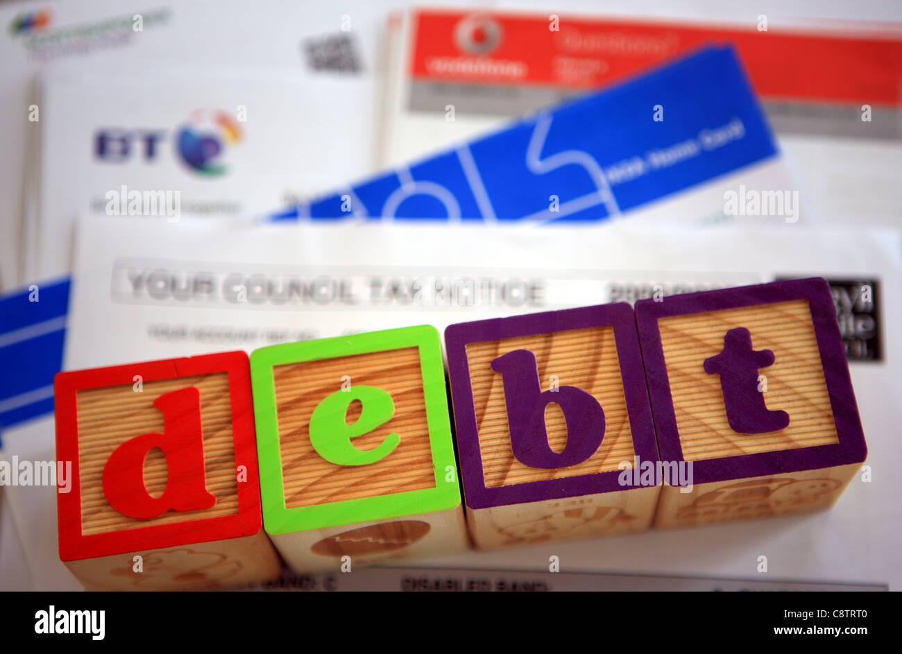 pile of bills with the word debt spelled out in building blocks on top of them Stock Photo