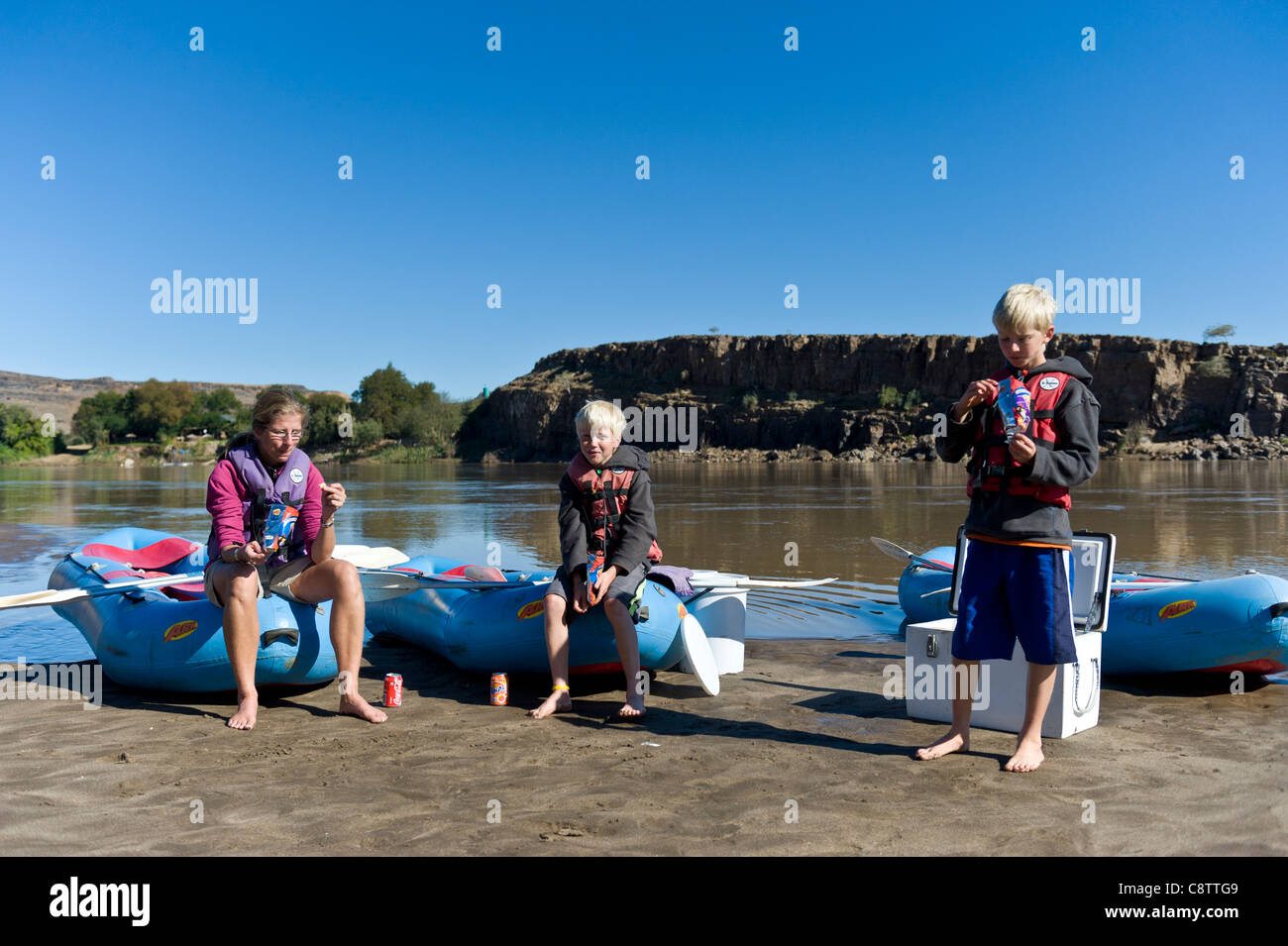 Mother and children enjoy a break during a rafting trip down the Oranje River at Noordoewer Namibia - Stock Image