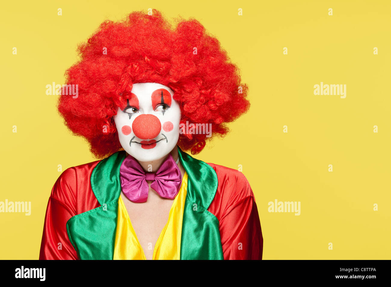 a female clown with colorful clothes and makeup - Stock Image