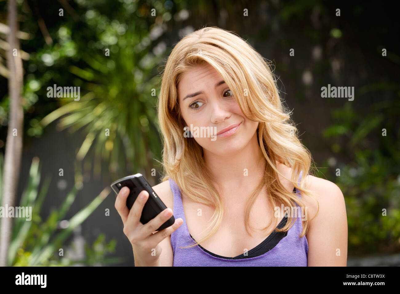 USA, California, Los Angeles, Young woman text-messaging, with facial expression - Stock Image