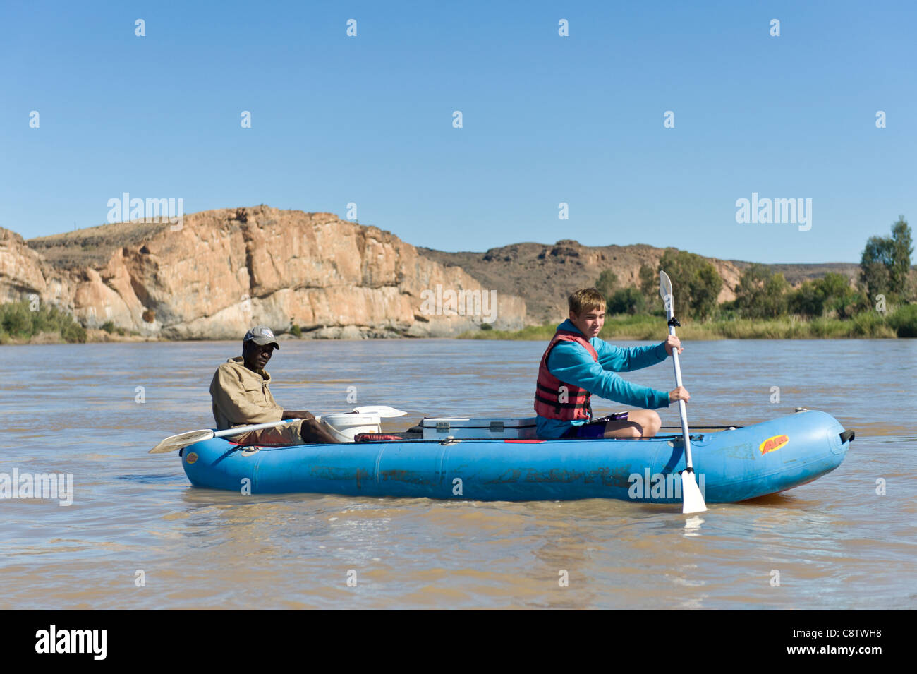 Tennager paddling with a guide on the Oranje River west of Noordoewer Namibia - Stock Image