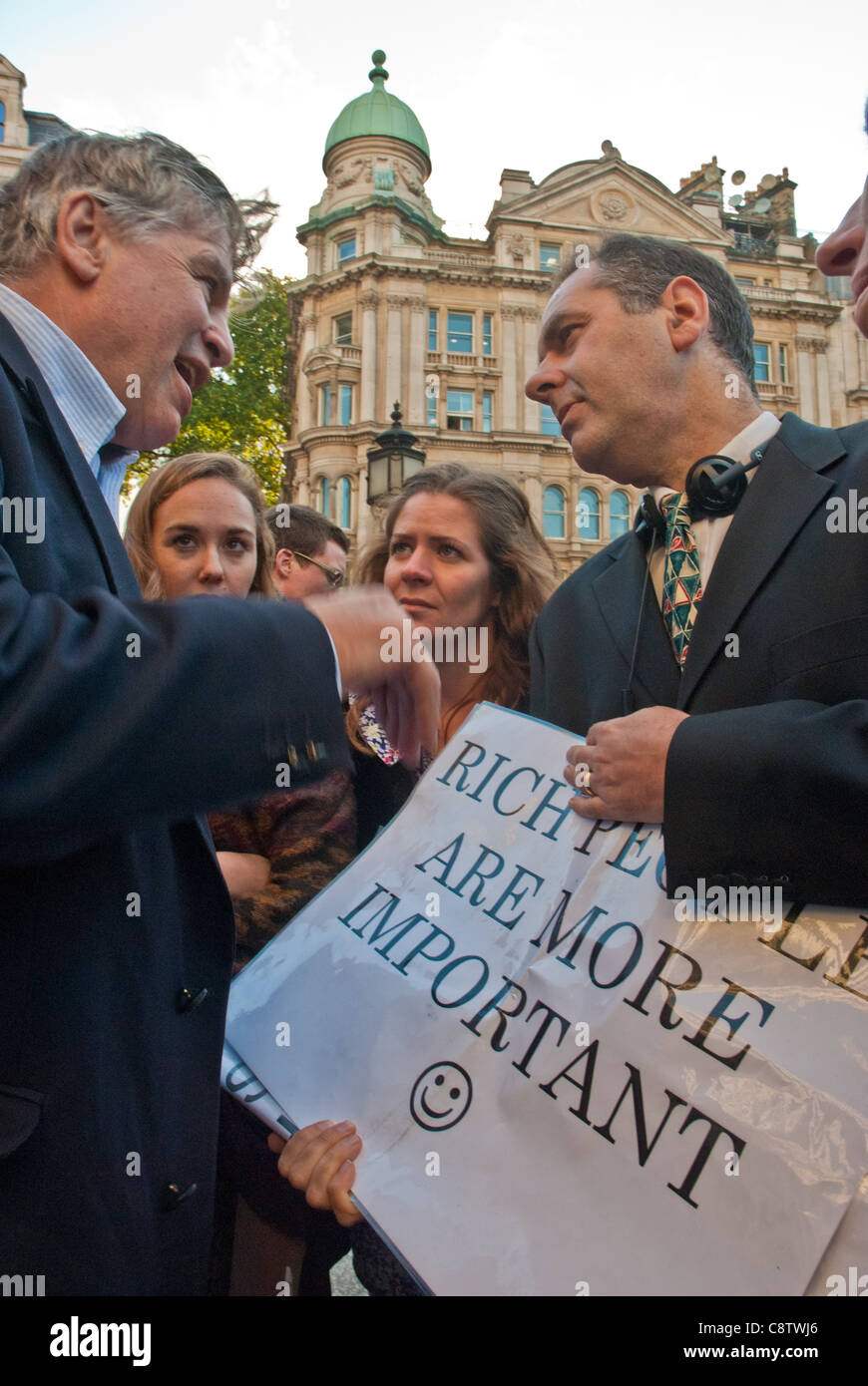 Occupy London. Two middle aged men in suits (bankers) have a serious discussion over a poster 'Rich people are - Stock Image