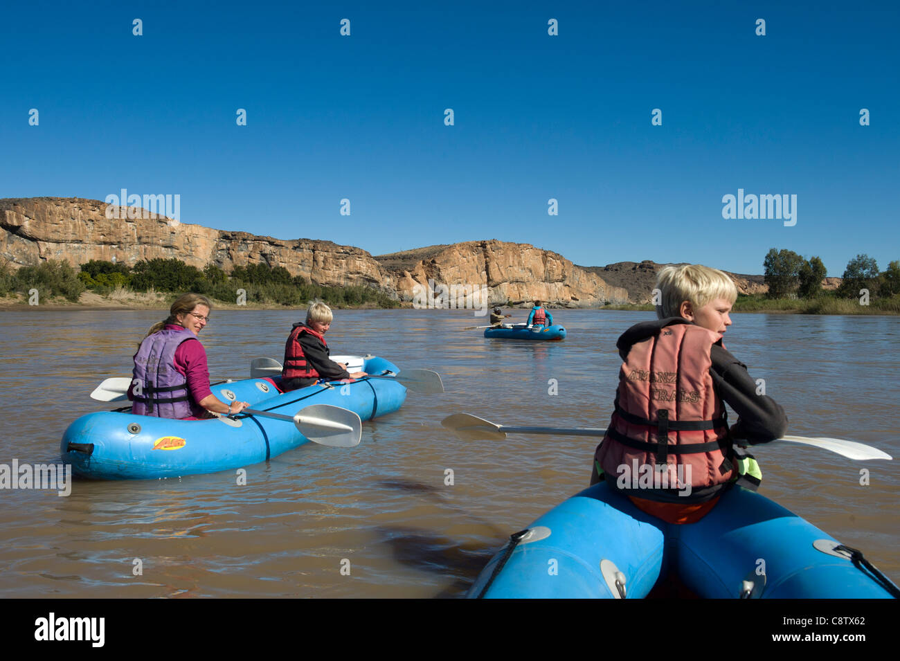 Mother and children enjoy paddling down the Oranje River at Noordoewer Namibia - Stock Image