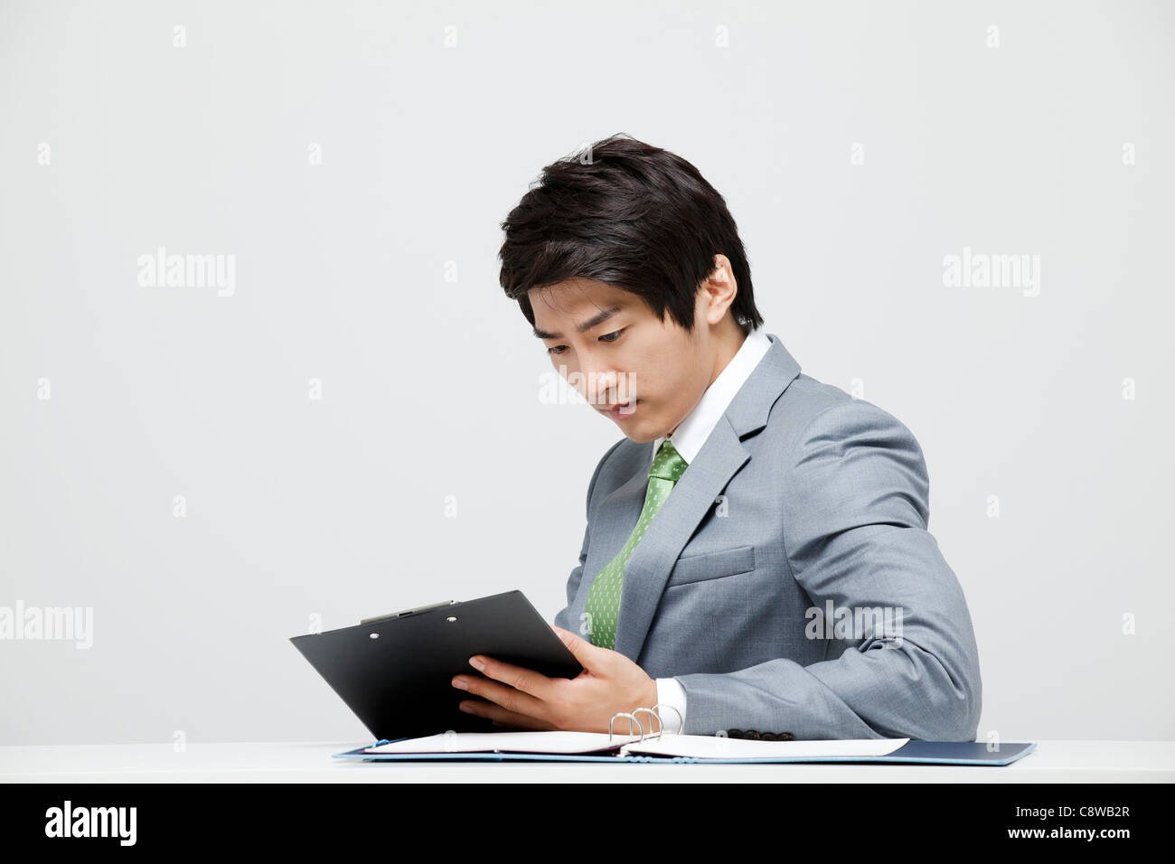 Asian Businessman Looking At Office Document - Stock Image
