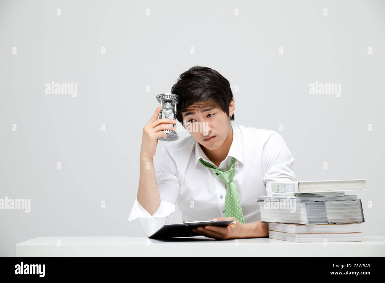 Asian Businessman Holding Hour Glass In Hand At Work Stock Photo