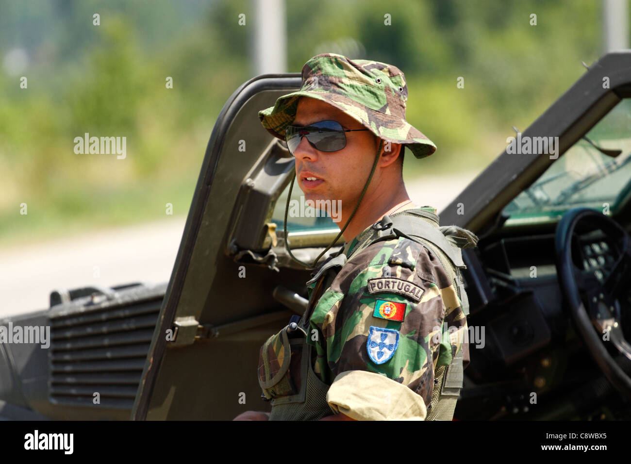Portuguese KFOR soldier in standing by his armored car in northern Kosovo - Stock Image