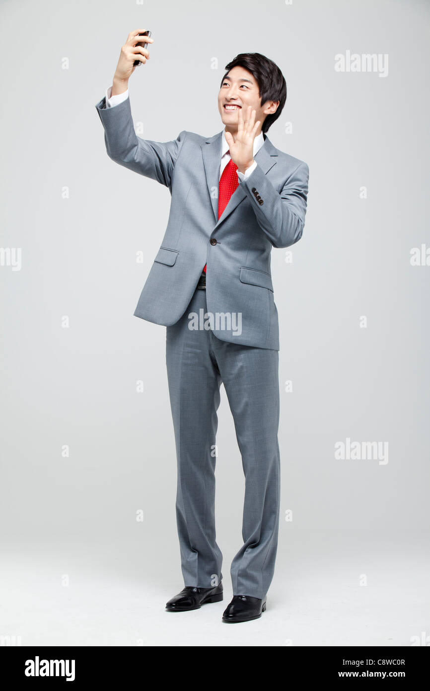 Asian Businessman  Taking Self-portrait With Cell Phone - Stock Image