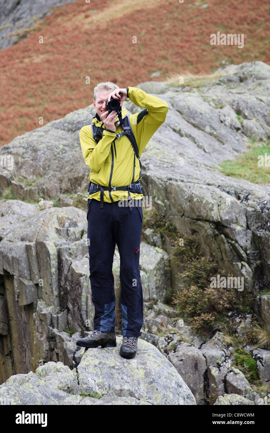 Alamy photographer stood on a rock outdoors taking a photograph of me with a digital SLR camera. England UK Britain. - Stock Image