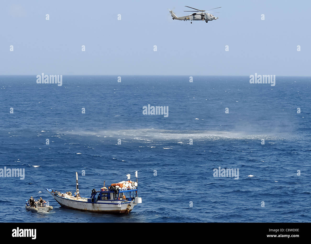 Vella Gulf (CG 72) use a rigid-hulled inflatable boat to approach a dhow needing assistance. - Stock Image