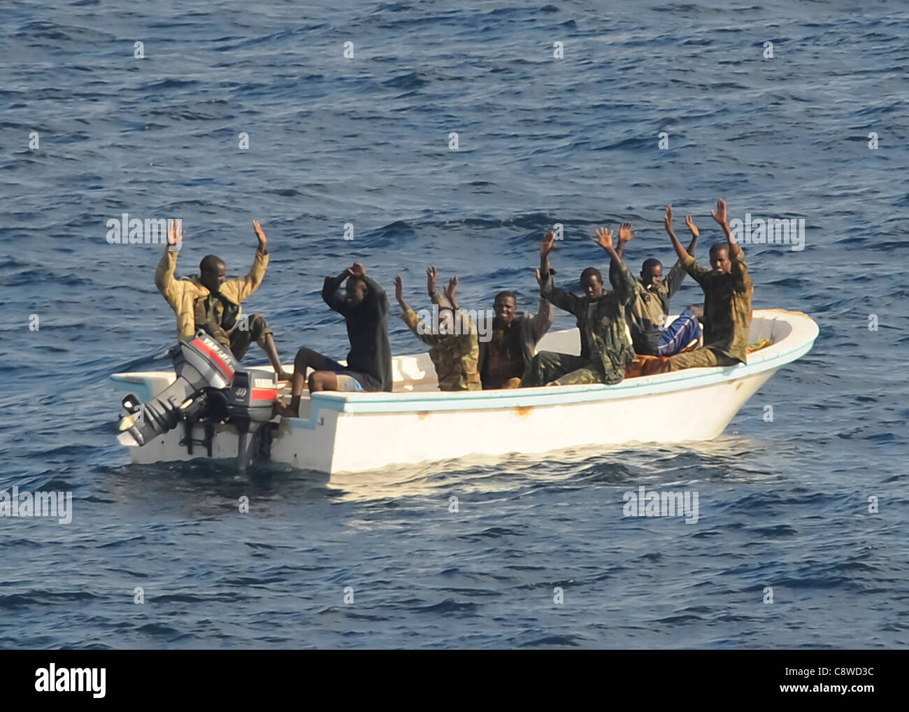 Suspected pirates keep their hands in the air as directed by the guided-missile cruiser USS Vella Gulf - Stock Image