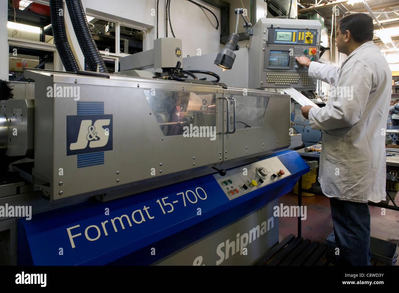 engineer prepares a metal grinding machine for work & programs - Stock Image